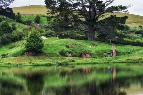 Отверстия в земле, ведущие в подземные жилища хоббитов в Хоббитоне, отражаются в небольшом озере. Снимок сделан в Новой Зеландии