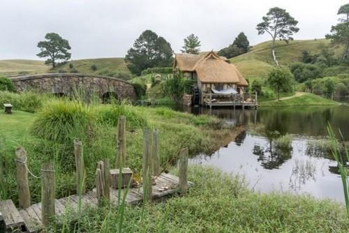 Мельница Хоббитона и двойной арочный мост, отражающиеся в озере. Новая Зеландия