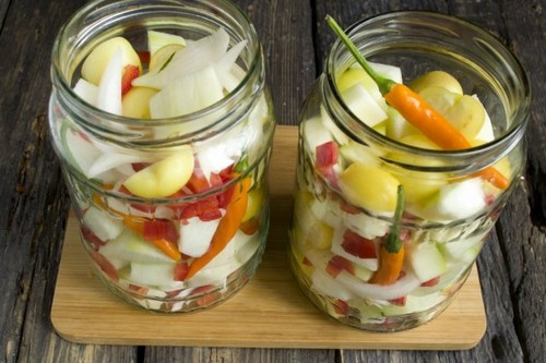 В чистые банки выкладываем овощную смесь, добавляем острый перец