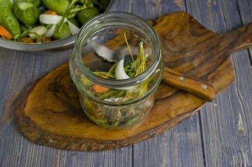 На дно банок укладываем подготовленную зелень, репчатый лук, и чеснок